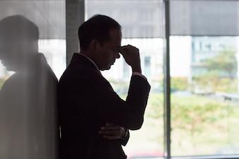 Silhouette di stressato uomo d'affari strofinando gli occhi