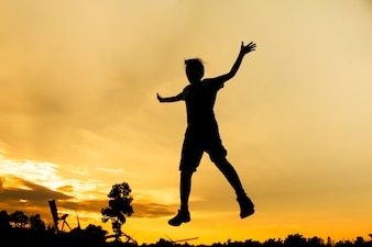 Silhouette di un ponticello sta saltando con il bello background di tramonto