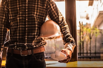Smart Businessman in possesso di casco di costruzione e cianografie in stile retrò.