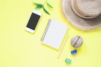 Smartphone con cappello, taccuino e matita su sfondo giallo, Overhead view shot