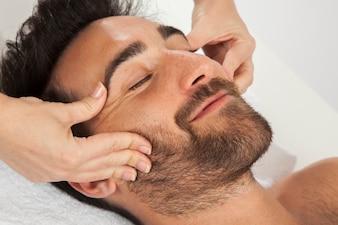 Smiley uomo durante il massaggio del viso