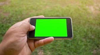 Soft focus della mano utilizzando smart phone mobile con sfondo sfocato.