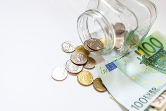 Soldi in vaso di vetro su priorità bassa bianca