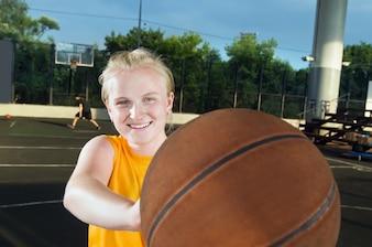 Sorridente adolescente con pallacanestro