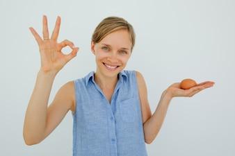 Sorridente donna che tiene uovo e che mostra il segno giusto