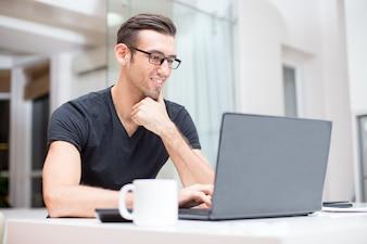 Sorridente giovane uomo bello che lavora al computer portatile