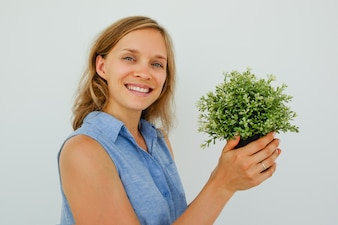 Sorridente Pretty Woman Holding Potted Plant