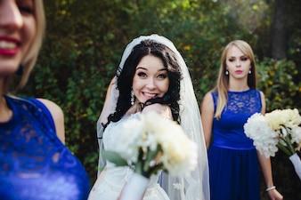 Sorridente sposa guardando fotocamera in posa