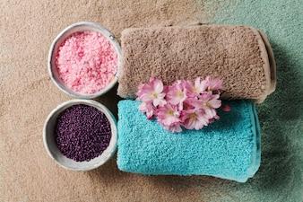 Spa Concept. Closeup di bellissimi prodotti Spa - sale da bagno, asciugamani e fiori. Orizzontale.