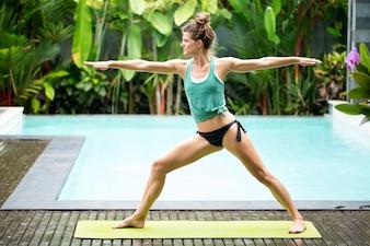 Sportiva, donna, fare, yoga, guerriero, due, posa, vicino, piscina