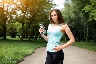 Sportswoman in un parco con una bottiglia d'acqua in mano