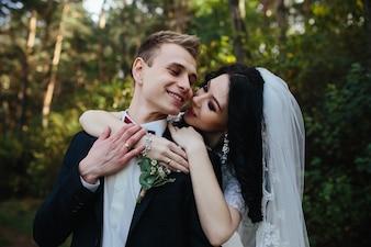 Sposa abbraccia sorridente fidanzato in piedi in legno