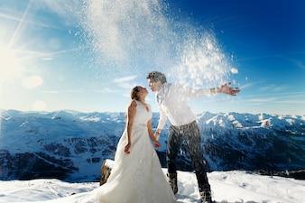 Sposa e sposo in amore lanciano neve sullo sfondo delle Alpi Courchevel