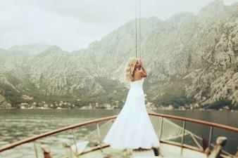 Sposa elegante alla moda bionda posa sul ponte di uno yacht sullo sfondo del mare e montagne Montenegro
