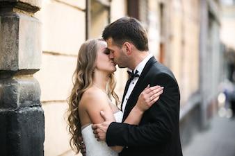 Sposo baciare bella sposa sulla strada