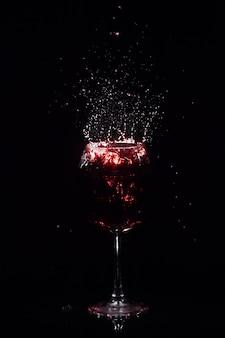 Spruzzi di succo di rosso volano intorno a bicchiere di vino di cristallo in piedi nello spazio scuro