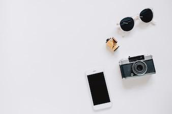 Stile creativo piatto piano con fotocamera, occhiali da sole e smartphone su sfondo bianco con spazio di copia