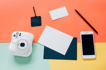 Stile piano piatto creativo dello scrittorio dello spazio di lavoro con la macchina fotografica istantanea, lo smartphone, la carta in bianco, il tag e la matita su priorità bassa minima del colore