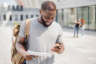 Studente allegro utilizzando il telefono