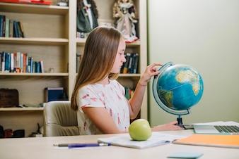 Studente in posa con globo a tavola
