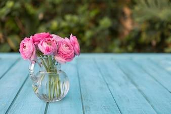 Superficie blu con fiori rosa sul vaso di vetro