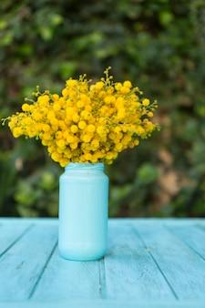 Superficie blu con i fiori in un vaso