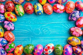 Superficie di legno blu con le uova di Pasqua cornice