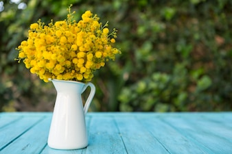 Superficie di legno con i fiori su un vaso di porcellana
