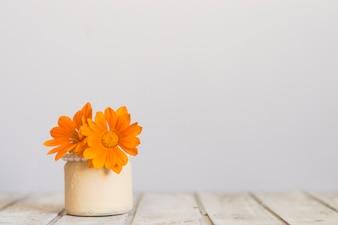 Superficie di legno con il vaso e fiori d'arancio impressionante