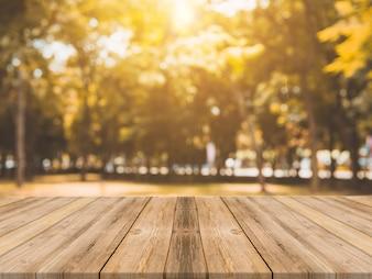 Tabella di legno vuota tabella di fronte a sfondo sfocato. Prospettiva tavola di legno marrone su sfocatura alberi in foresta di fondo - può essere utilizzato mock up per visualizzare o montare i tuoi prodotti. stagione autunnale.