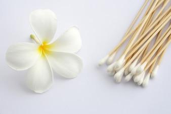 Tamburo di cotone usato per la pulizia dell'orecchio e fiori tropicali isolati su bianco