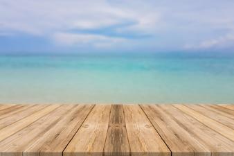 Tavola di legno bordo vuoto sfuocatura mare e cielo sfondo. Prospettiva sfondo marrone tavolo in legno marrone - può essere utilizzato per la presentazione dei prodotti montage o la progettazione visuale della chiave di design. Concetti estivi.