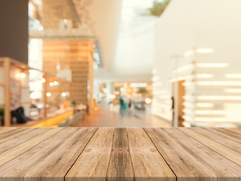 Tavola di legno tabella vuota su sfondo sfocato. Prospettiva tavolo di legno marrone sulla sfocatura nella priorità bassa del caffè - può essere usato mock up per la visualizzazione dei prodotti di montaggio o la disposizione di disegno chiave del disegno.