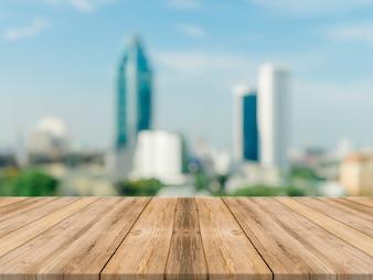Tavola di legno tavolo vuoto vuoto sfondo sfocato. Prospettiva tavolo di legno marrone sulla sfocatura della città vista della costruzione vista - può essere utilizzato mock up per la visualizzazione di prodotti di montaggio o design chiave layout visivo.