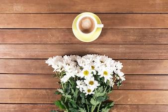Tavole di legno con tazza di caffè e fiori