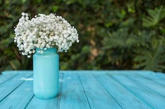 Tavole superficie blu con i fiori su un vaso