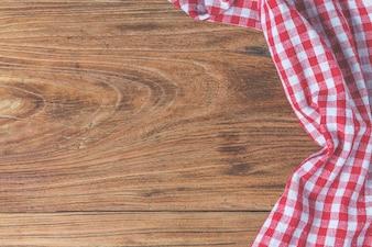 Tavolo di legno vuoto e tovagliolo rosso di panno