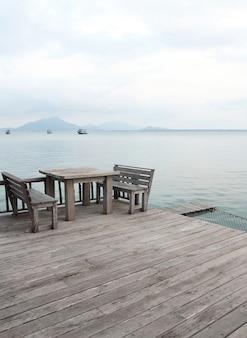 Tavolo e sedie in legno su una spiaggia tropicale