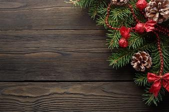 Tavolo in legno scuro con ramo di pino e una pigna