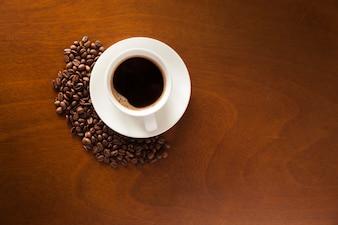 Tazza di caffè e fagioli su legno
