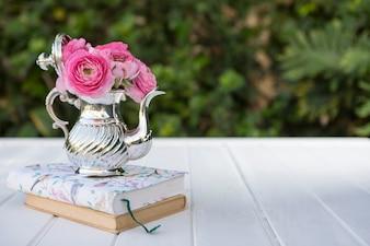 Teiera con fiori su alcuni libri