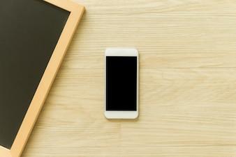 Telefono cellulare con schermo vuoto e telaio di lavagna in legno vuoto sullo sfondo della tavola di legno. Vista superiore con spazio di copia. Può essere utilizzato l'immagine di mock up. Immagini di stile d'effetto vintage.