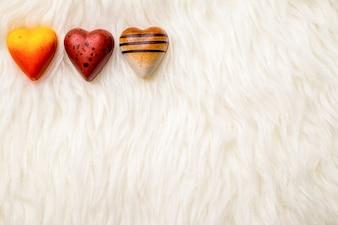 Tema di San Valentino: cioccolato a forma di cuore sulla trama di pelliccia.