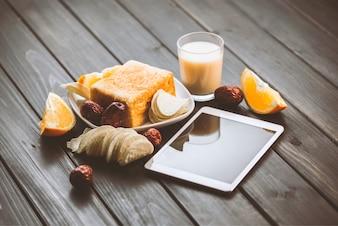 Toast, bicchiere di latte e un tablet