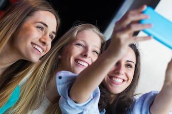 Tre amici che scattano fotografie con uno smartphone