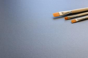Tre spazzole verniciate, isolate su sfondo grigio scuro.