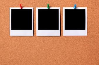 Tre stampe fotografiche polaroid appuntate ad una bacheca di sughero