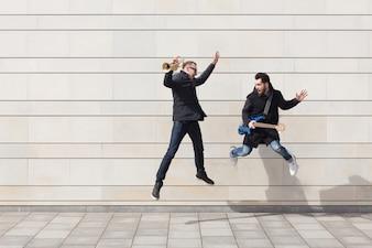 Tromba giocatore e chitarrista saltando in ambiente urbano
