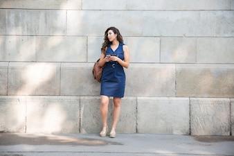 Turista serio femminile con sacchetto in attesa di taxi