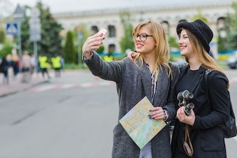 Turisti donne che si prendono selfie con la mappa